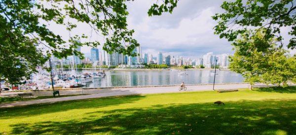 Un hombre en bicicleta frente al skyline de Vancouver.