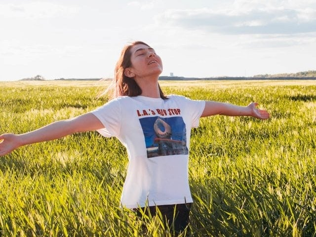 A girl breathing happily in the field.