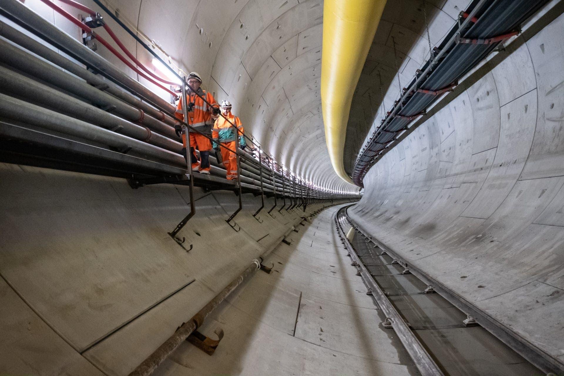 Foto del interior de un túnel con 2 operarios caminando dentro