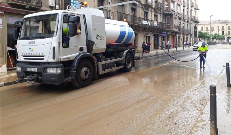 Photo of a cleaning worker and a truck cleaning a street in Tafalla after the floods
