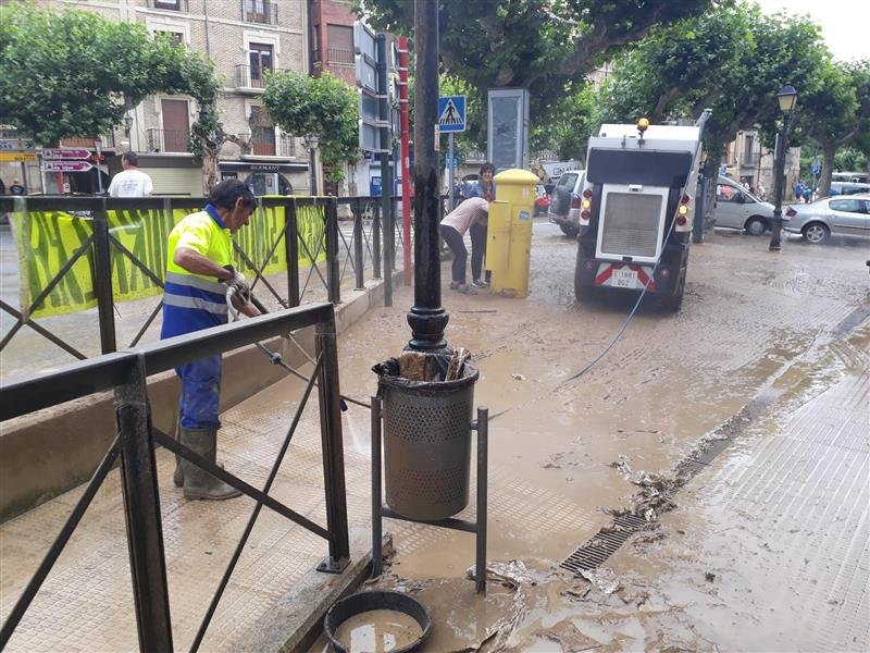 Photo of a cleaning worker working on a muddy street after the floods