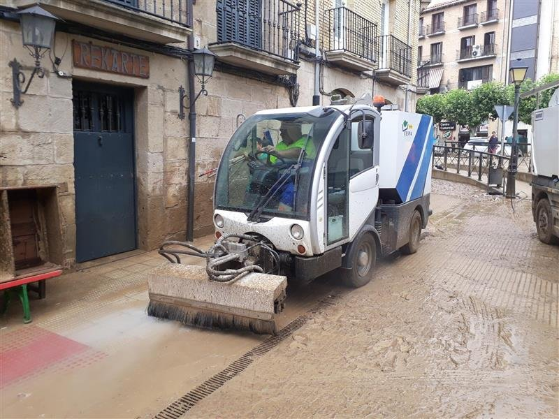 Photo of cleaning machinery doing work on a muddy street
