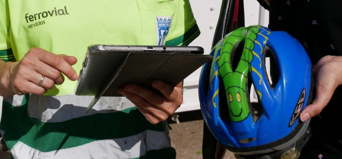 Photo of a person with a bike helmet in his hand and an employee of Ferrovial Services taking note on a tablet