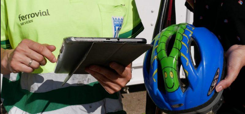 Foto de una persona con un casco de bici en la mano y un empleado de Ferrovial Servicios tomando nota en una tablet