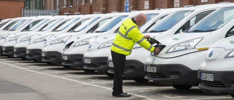 Imagen de un operario comprobando un coche en un aparcamiento de coches eléctricos