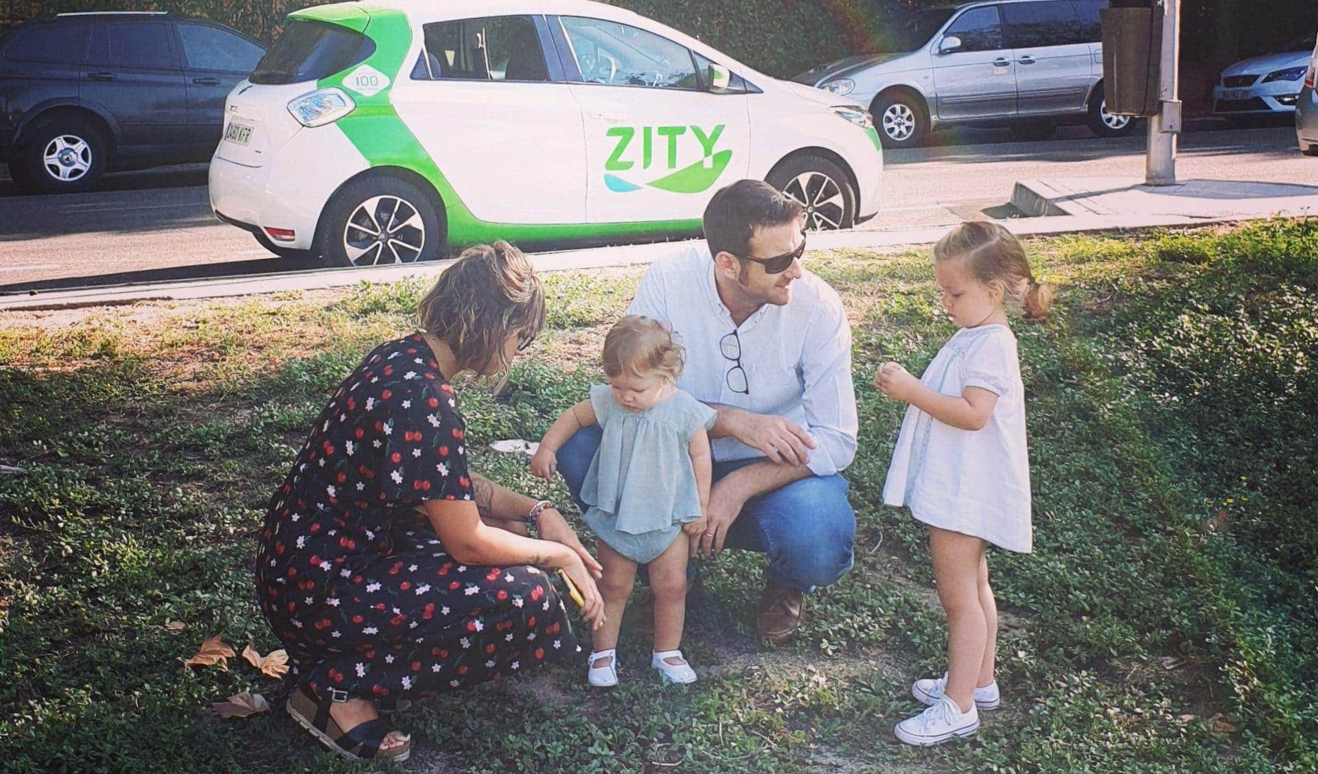 Image of a family with two children in front of a Zity car