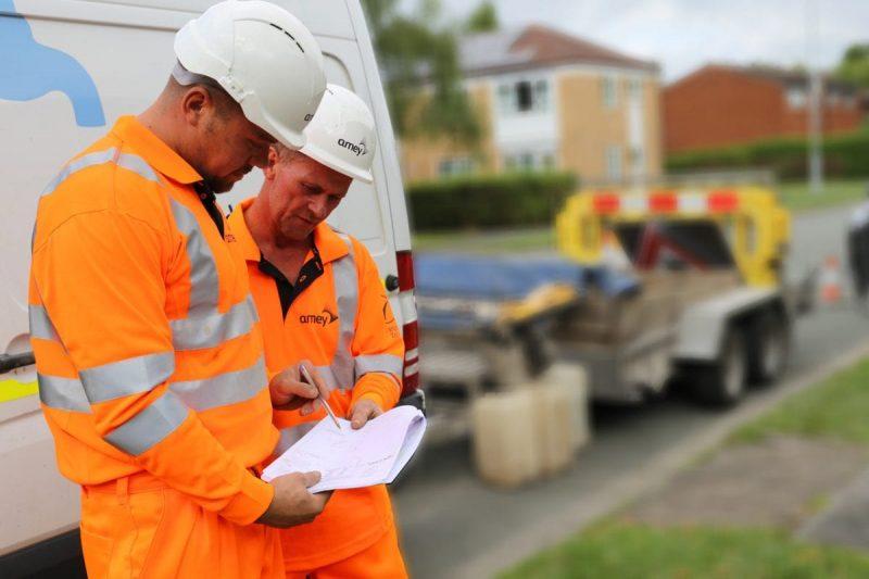 Foto de 2 operarios mirando unos planos