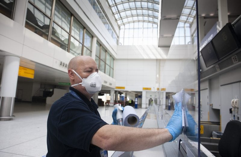 Man cleans Heathrow airport covid 19 measures safety